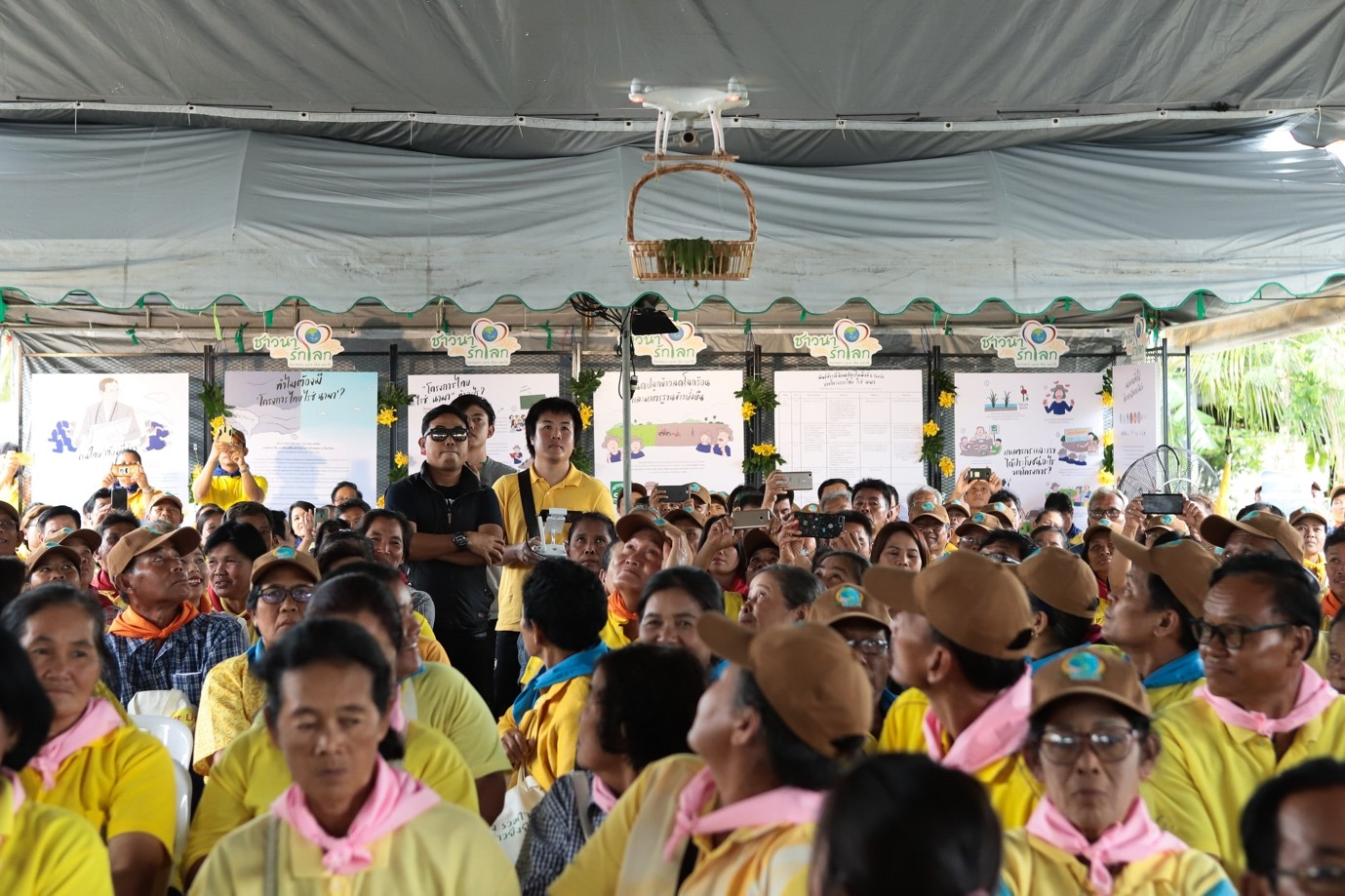 Farmers look at the drone carrying rice seedlings during the opening ceremony. (Photo credit: GIZ Thailand)