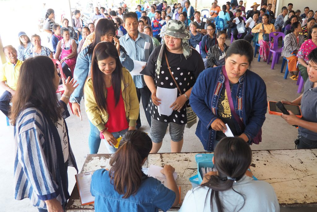 Local farmers have their ID cards checked before receiving the bonuses. (Photo credit: GIZ Thailand)