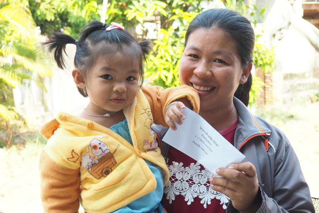 A farmer from Samrong district of Ubon Ratchathani province takes her daughter to the community hall to receive the bonus together.